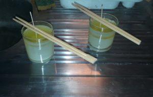 Refroidissement de la cire des bougies, versée dans les bougeoirs, la mèche maintenue droite par des baguettes asiatiques.