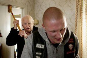 Vieux voyou s'apprêtant à fracasser le crâne d'un jeune homme. Le Vieux qui ne voulait pas fêter son anniversaire.
